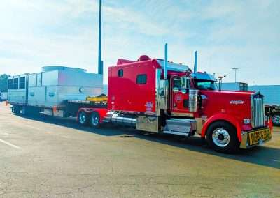 Red kenworth truck with large sleeper pulling large load